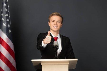 Photo pour Homme souriant montrant pouce vers le haut sur tribune avec drapeau américain sur fond noir - image libre de droit