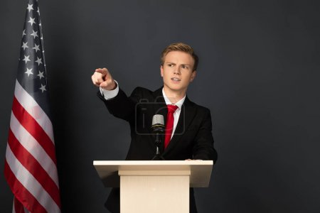 Photo for Emotional man pointing with finger on tribune with american flag on black background - Royalty Free Image