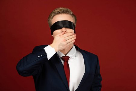 Photo pour Man with blindfold on eyes covering mouth with hand on red background - image libre de droit