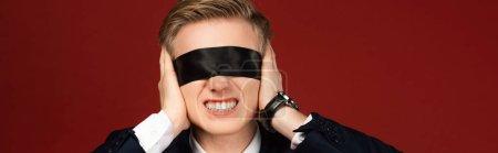 Photo pour Homme avec bandeau sur les yeux couvrant les oreilles avec les mains sur fond rouge - image libre de droit