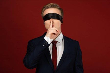 Photo pour Homme avec les yeux bandés montrant un geste shh sur fond rouge - image libre de droit