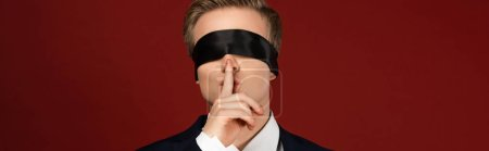 Photo pour Man with blindfold on eyes showing shh gesture on red background - image libre de droit