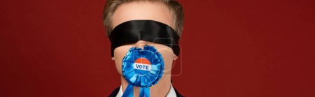 man with blindfold on eyes and badge with vote lettering in mouth on red background