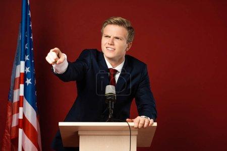 Photo pour Homme émotionnel pointant du doigt sur la tribune près d'un drapeau américain sur fond rouge - image libre de droit