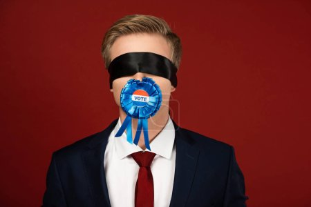 Photo for Man imitating with blindfold on eyes and badge with vote lettering in mouth on red background - Royalty Free Image