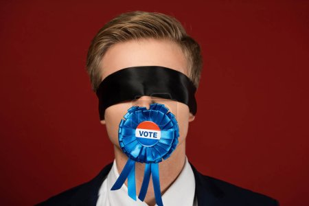 Photo pour Man with blindfold on eyes and badge with vote lettering in mouth on red background - image libre de droit
