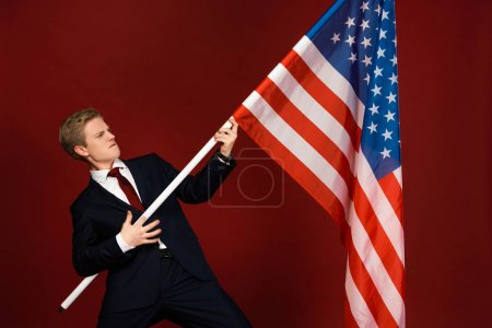 emotional man holding american flag on red background