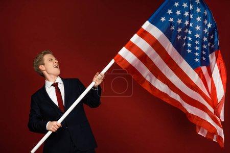 Photo pour Homme émotionnel tenant un drapeau américain sur fond rouge - image libre de droit