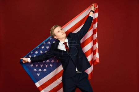 dreamy man holding american flag on red background