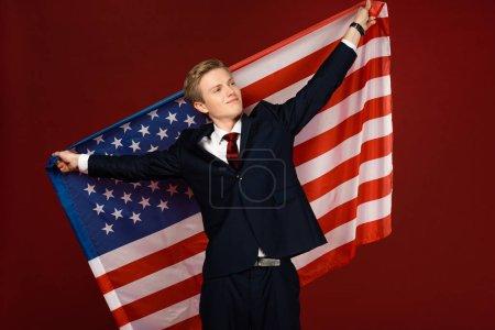 Photo pour Homme souriant tenant drapeau américain sur fond rouge - image libre de droit