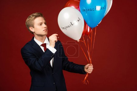 Photo pour Man bursting balloons with impeachment lettering on red background - image libre de droit