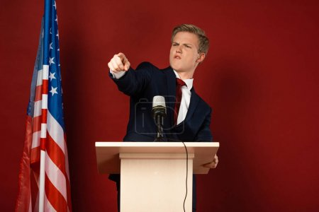 Photo pour Emotional man pointing with finger on tribune near american flag on red background - image libre de droit