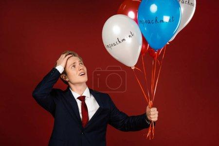 Photo pour Homme inquiet tenant des ballons avec lettrage de destitution sur fond rouge - image libre de droit