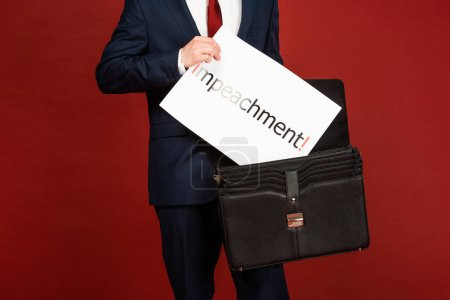 Photo pour Kyiv, Ukraine - October 18, 2019 : cropped view of man imitating Donald Trump taking white card with impeachment lettering from leather case on red background - image libre de droit