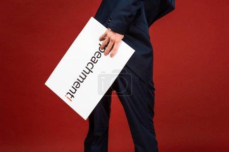 Photo pour Vue recadrée de l'homme tenant une carte blanche avec inscription de destitution sur fond rouge - image libre de droit