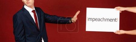 Photo pour Vue recadrée de l'homme ne montrant aucun geste à la carte blanche avec lettrage de destitution sur fond rouge - image libre de droit