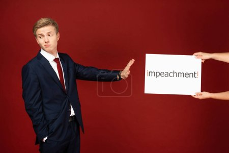 Photo pour Kyiv, Ukraine - 18 octobre 2019 : emotional man imitating Donald Trump showing no gesture to white card with impeachment lettering on red background - image libre de droit
