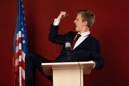 Photo pour Homme émotionnel montrant geste oui sur tribune près drapeau américain sur fond rouge - image libre de droit