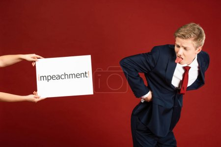 Photo pour Man showing ass and tongue to white card with impeachment lettering on red background - image libre de droit