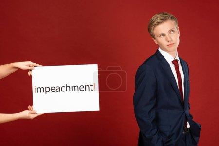 Photo pour Homme sceptique près de carte blanche avec lettrage de destitution sur fond rouge - image libre de droit