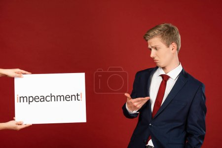 Photo pour Skeptical man looking at white card with impeachment lettering on red background - image libre de droit