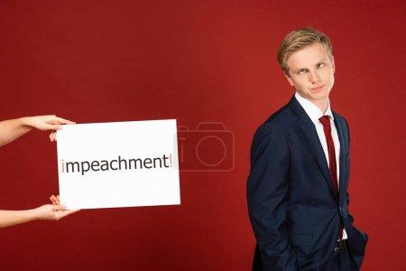 Photo pour Homme sceptique grimaçant près de carte blanche avec lettrage de destitution sur fond rouge - image libre de droit