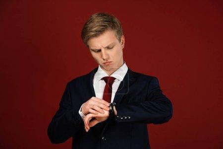 Photo pour Homme regardant montre-bracelet sur fond rouge - image libre de droit