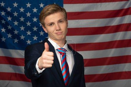 Photo pour Homme montrant pouce vers le haut sur fond drapeau américain - image libre de droit