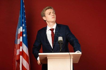 Photo pour Homme sérieux debout sur tribune près du drapeau américain sur fond rouge - image libre de droit