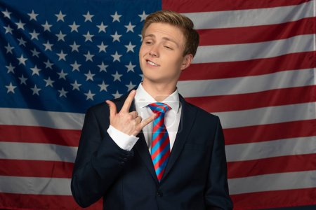 Photo for Man showing rock gesture on american flag background - Royalty Free Image