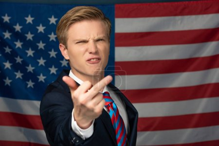 Photo for Angry man showing middle finger on american flag background - Royalty Free Image