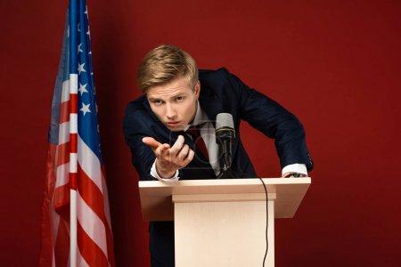 Photo pour Homme sérieux pointant du doigt la caméra sur tribune près du drapeau américain sur fond rouge - image libre de droit