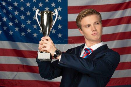 Photo pour Man holding golden goblet on american flag background - image libre de droit