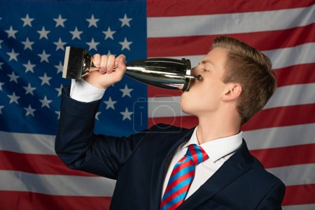 Photo pour Man drinking from golden goblet on american flag background - image libre de droit