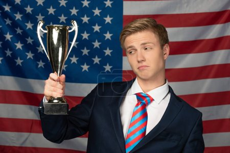 man holding golden goblet on american flag background