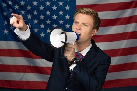 Foto de Hombre gritando en megáfono en el fondo de la bandera estadounidense - Imagen libre de derechos