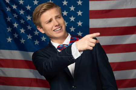 Photo pour Smiling man pointing with finger away on american flag background - image libre de droit