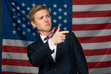 Photo pour Man pointing with finger away on american flag background - image libre de droit