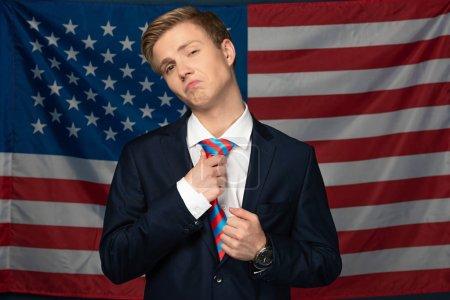 Photo pour Homme sérieux touchant cravate sur fond drapeau américain - image libre de droit