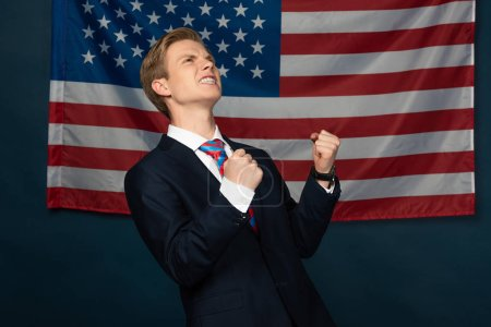 Photo pour Excited man showing yes gesture on american flag background - image libre de droit