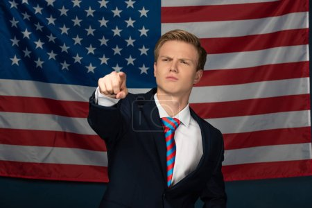 Photo for Serious man pointing with finger on american flag background - Royalty Free Image