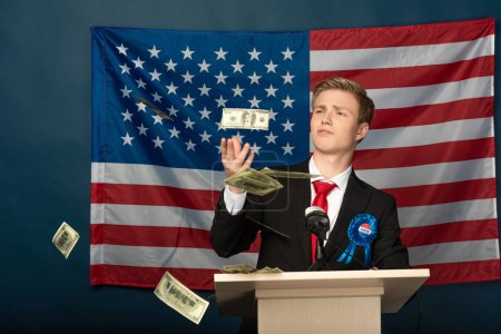 Photo pour Homme jetant de l'argent sur tribune sur fond de drapeau américain - image libre de droit