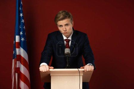 Photo pour Serious man on tribune near american flag on red background - image libre de droit