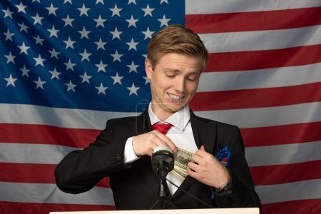 Photo pour Kyiv, Ukraine - October 18, 2019 : man imitating Donald Trump holding cash on tribune on american flag background - image libre de droit