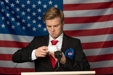 Photo pour Homme regardant tasse de café sur tribune sur fond drapeau américain - image libre de droit