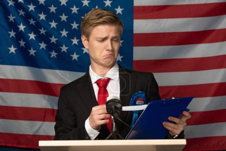 emotional man looking at clipboard on tribune on american flag background