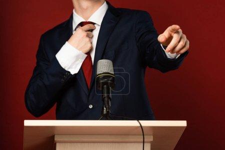 Photo pour Vue recadrée de l'homme pointant du doigt sur tribune sur fond rouge - image libre de droit