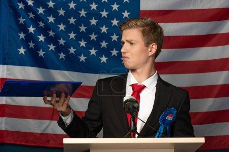 Photo pour Émotionnel homme holing presse-papiers sur tribune sur fond de drapeau américain - image libre de droit