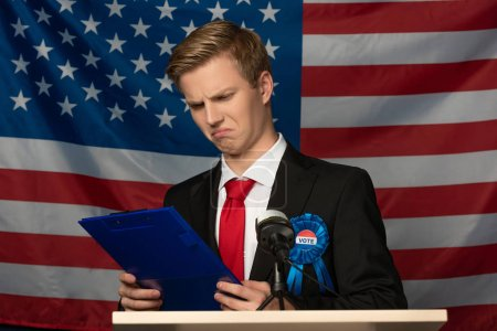 Photo pour Emotional man looking at clipboard on tribune on american flag background - image libre de droit