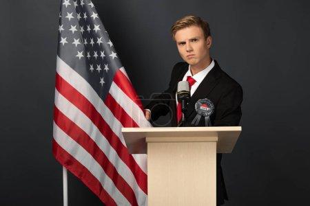 Photo pour Homme sérieux sur tribune avec drapeau américain sur fond noir - image libre de droit